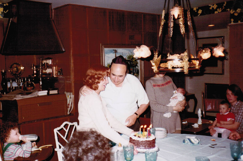 Nanny and Papa celebrating a birthday at home in Columbus—Mom holding infant me at Papa's left, 1982