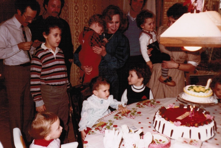 My first birthday at Dad's house in Columbus, Ohio—me center (blue dress), Nanny behind me, cousins Isaac and Evan to my left, 1983