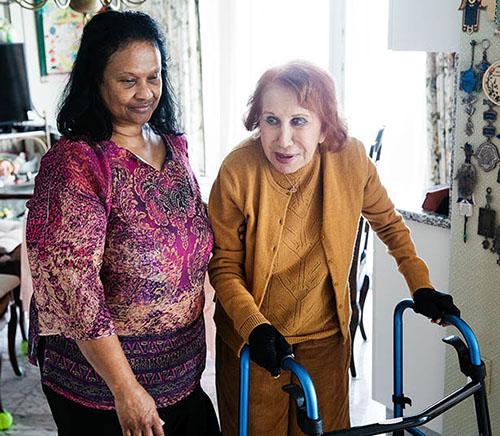 Beverley Schottenstein walks alongside her caretaker Dawn Henry in the kitchen of her condominium in Bal Harbour, Florida, U.S., on Wednesday, Dec. 30, 2020. Photographer: Scott McIntyre/Bloomberg